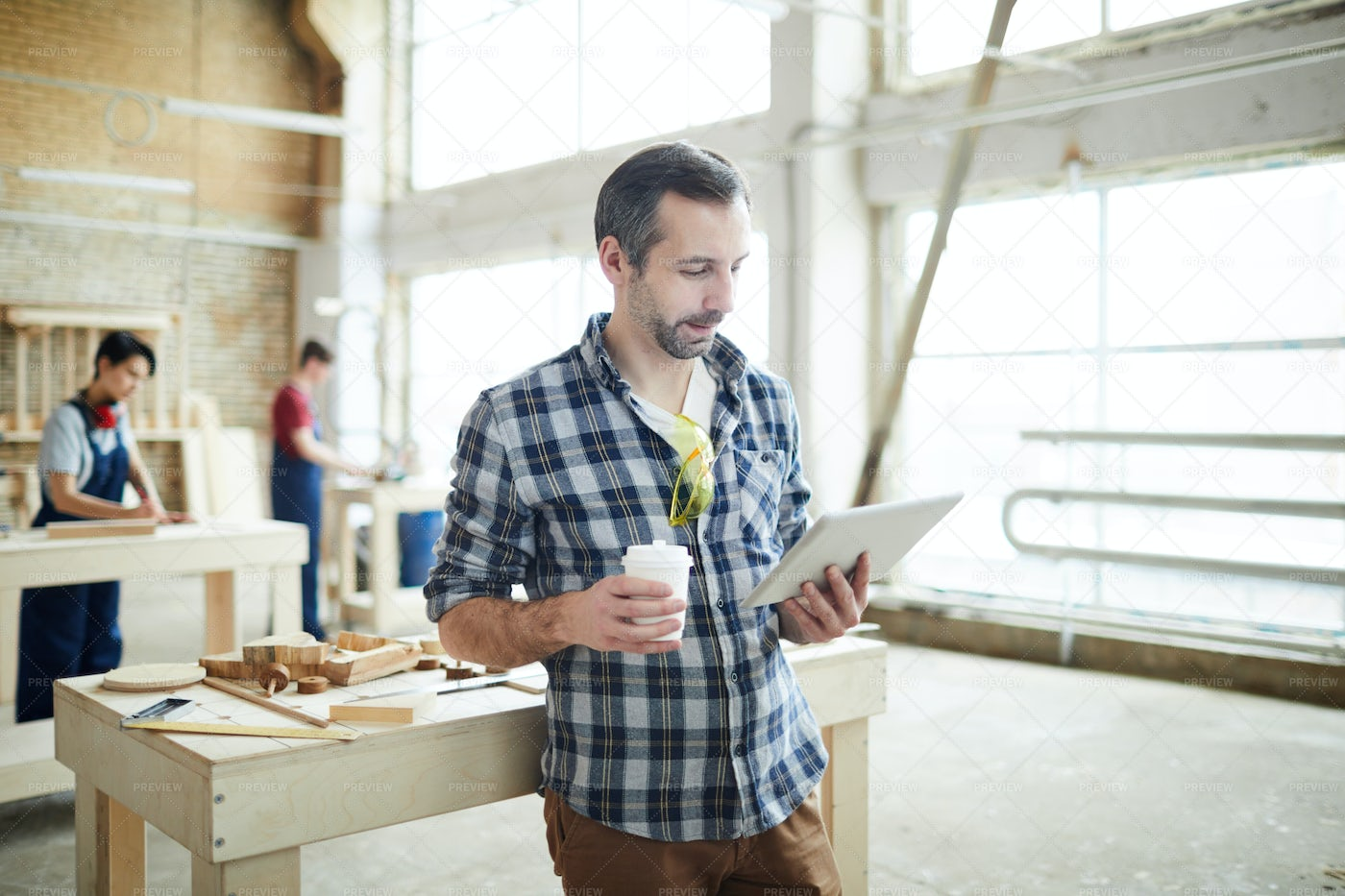 Busy Young Joiner Reading Article...: Stock Photos