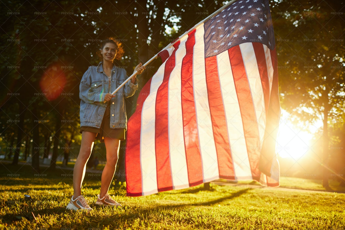 Girl Waving National Flag In Forest: Stock Photos
