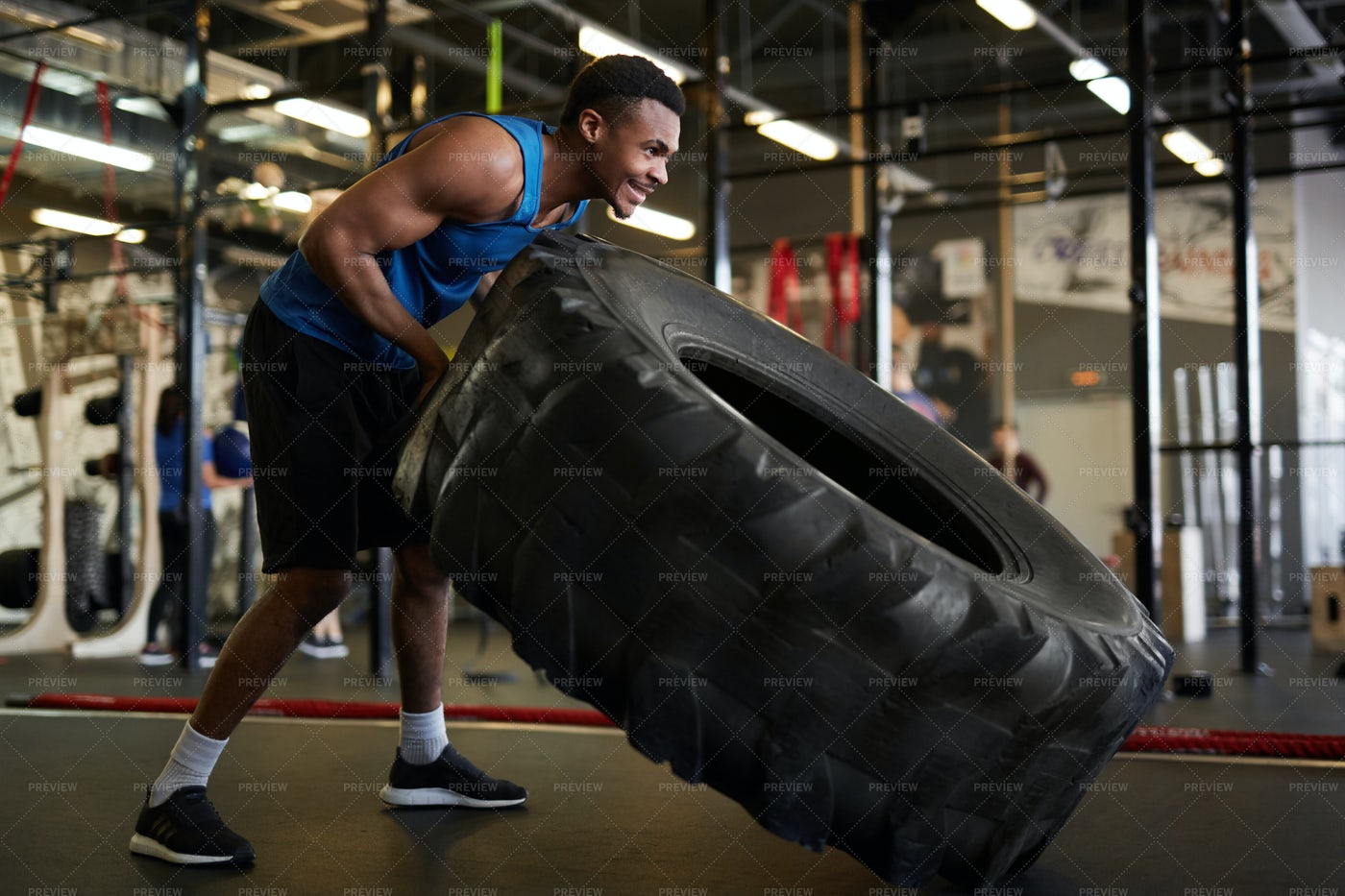 Strong Man Flipping Tire In Gym: Stock Photos