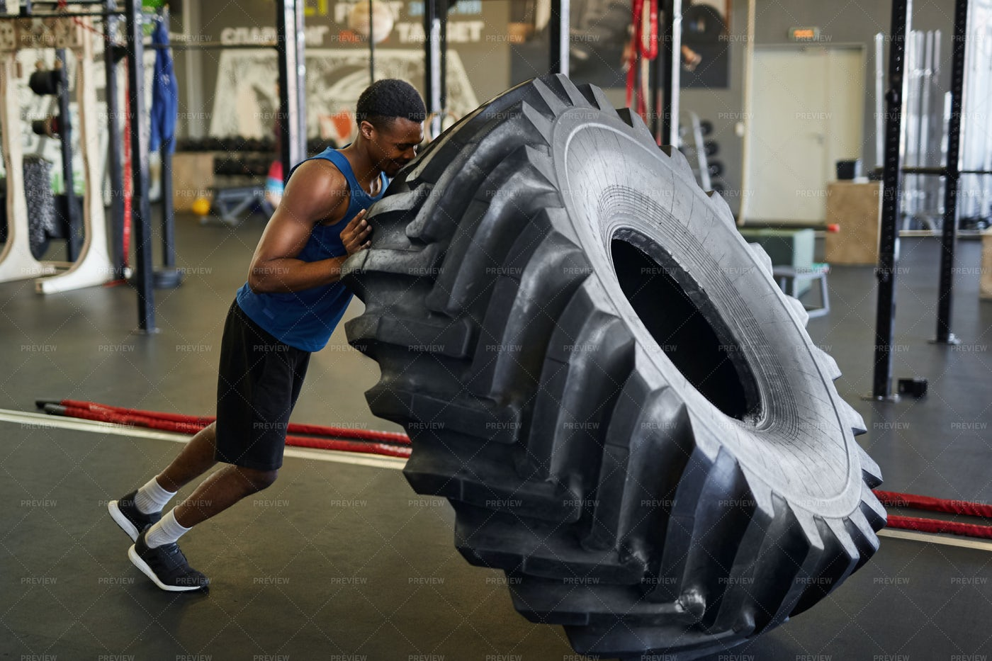 Sportsman Flipping Tire In Gym: Stock Photos