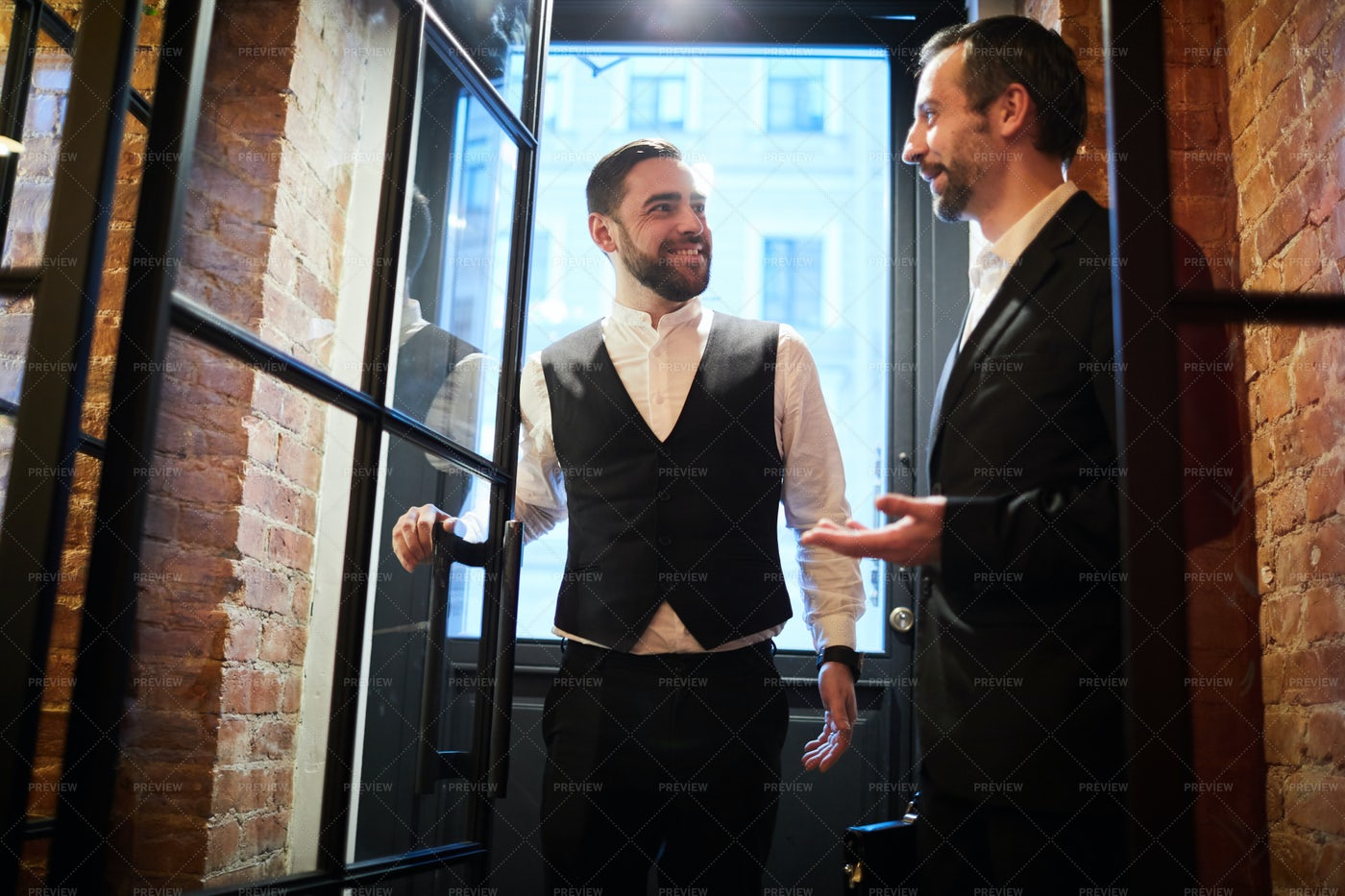 Two Business People Enter Door: Stock Photos