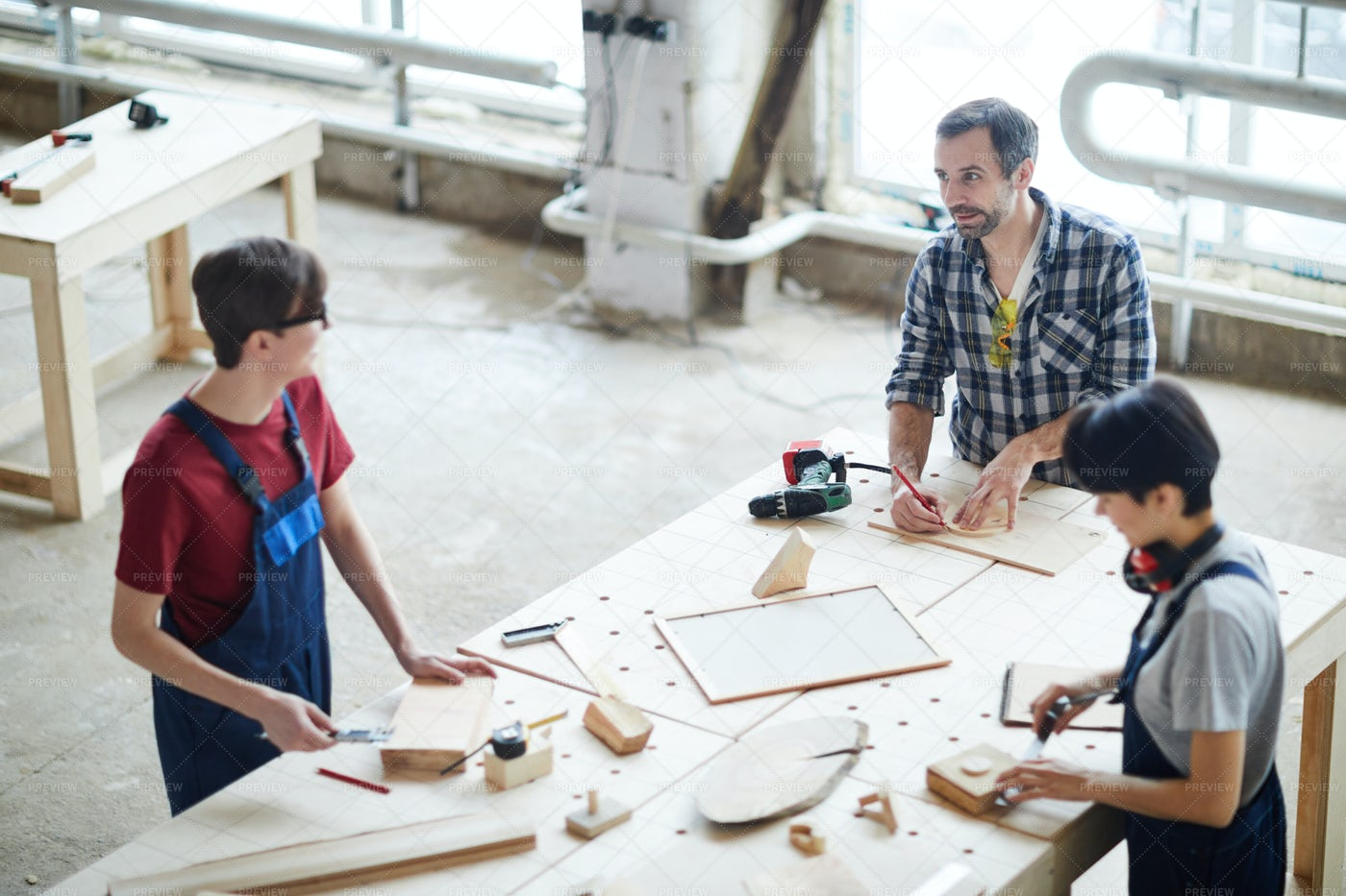 Carpenters Chatting While Working: Stock Photos