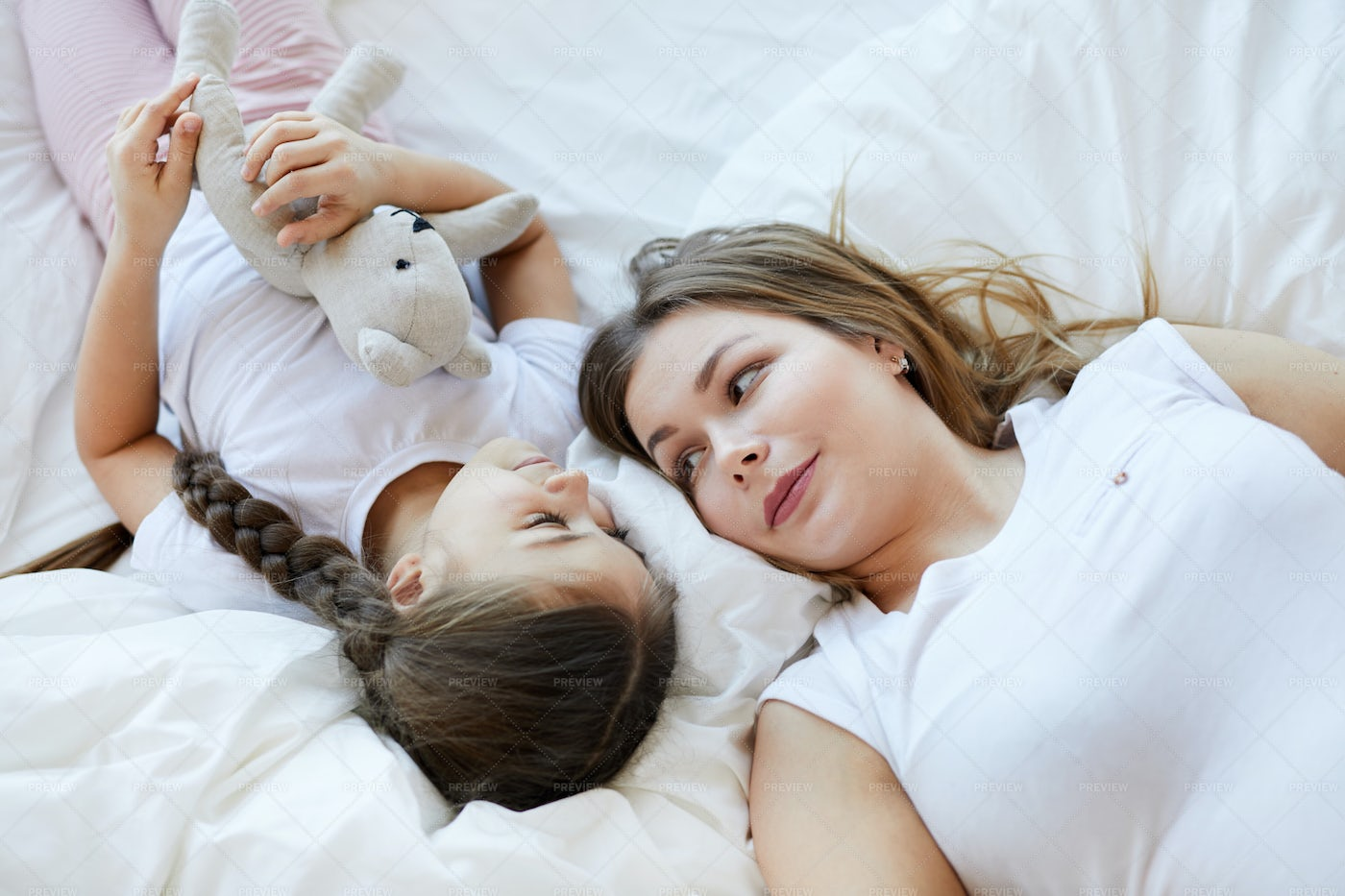 Mother And Daughter Lying On Bed: Stock Photos