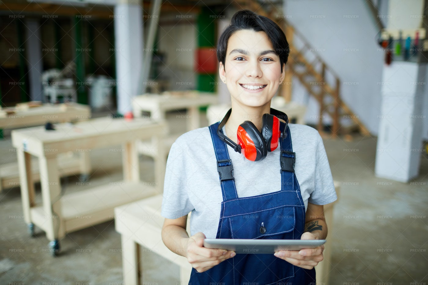 Smiling Female Carpenter With Tablet: Stock Photos