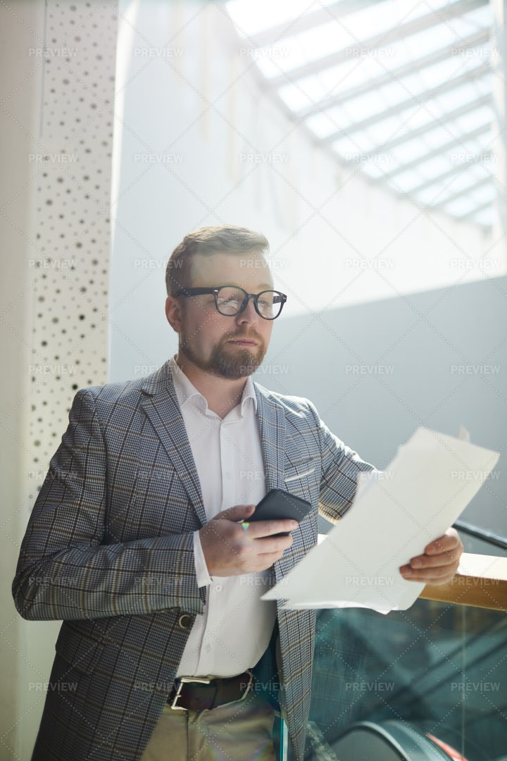 Serious Businessman Examines Papers: Stock Photos