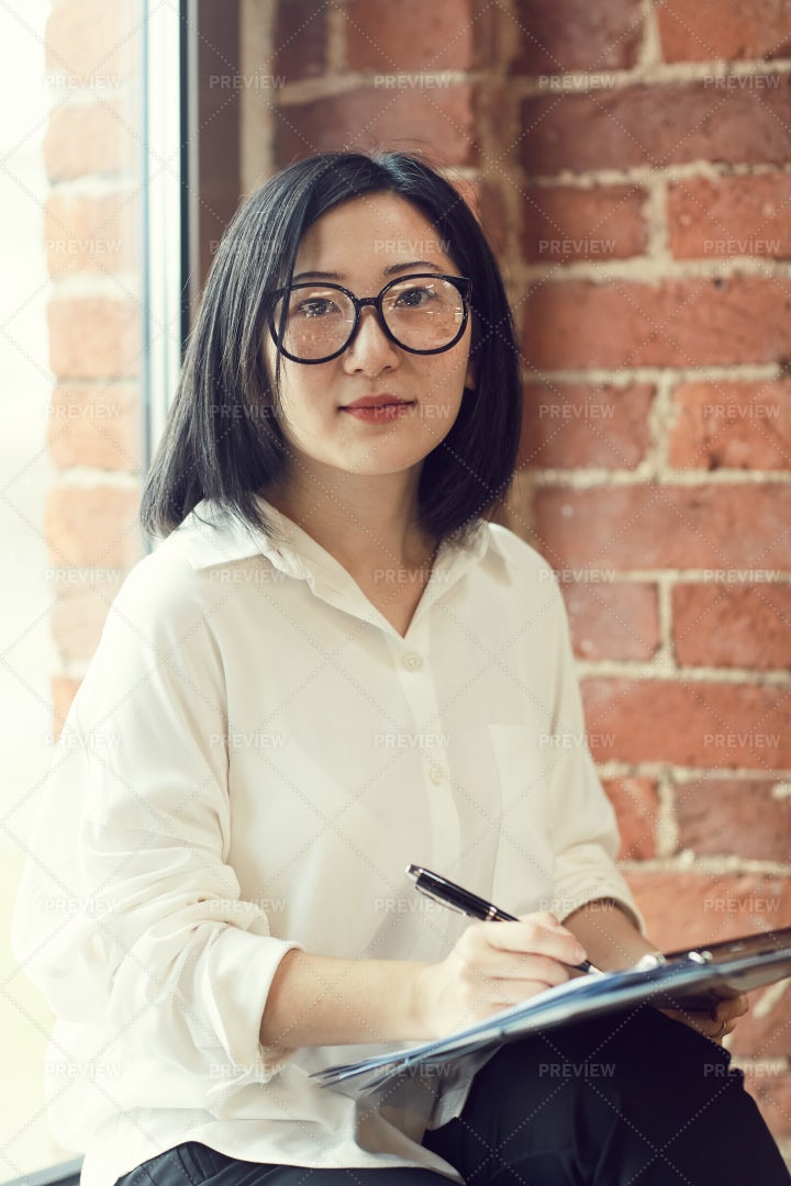 Asian Businesswoman Looking At...: Stock Photos
