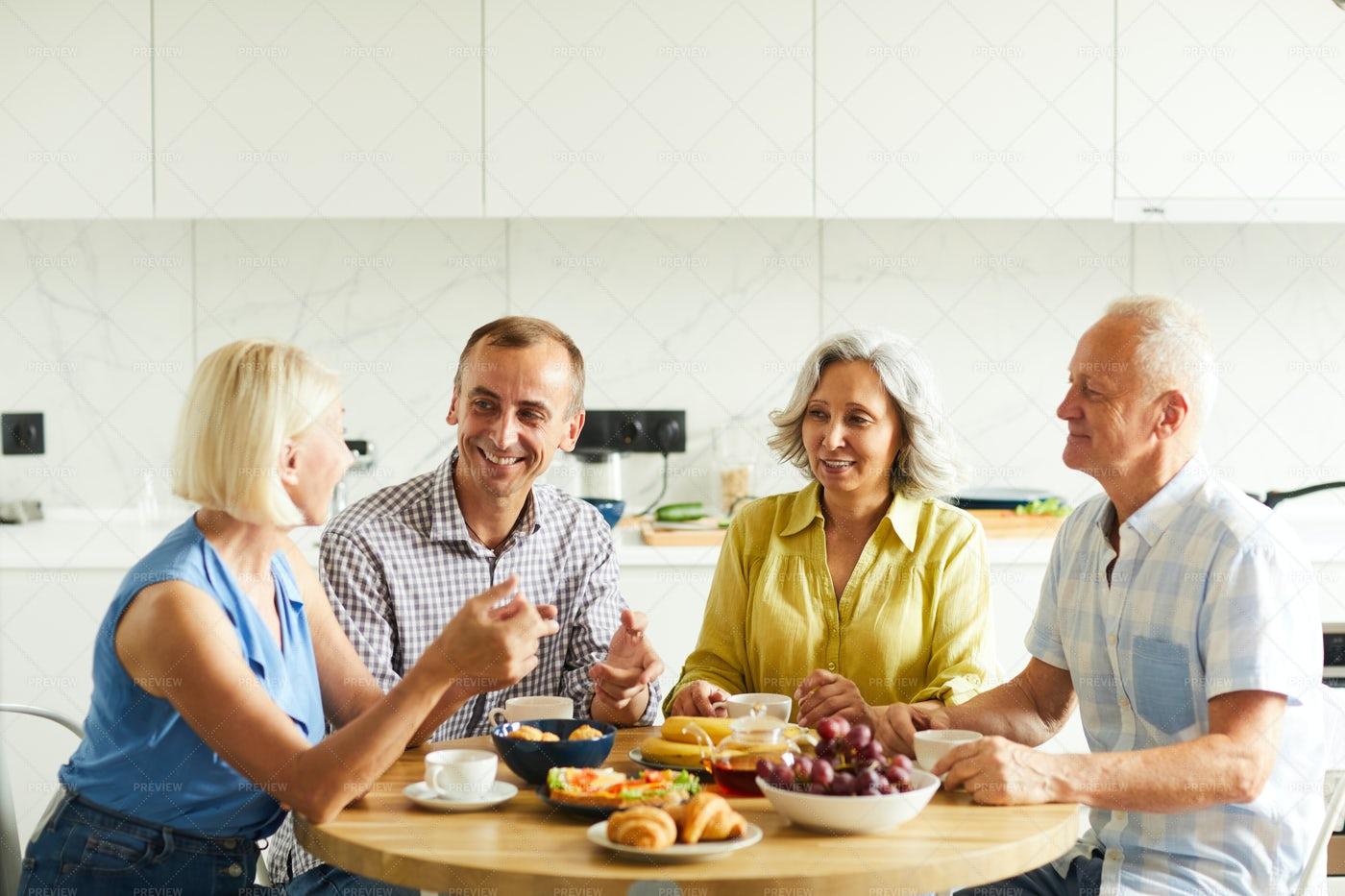 Mature Friends Gathered At Kitchen...: Stock Photos