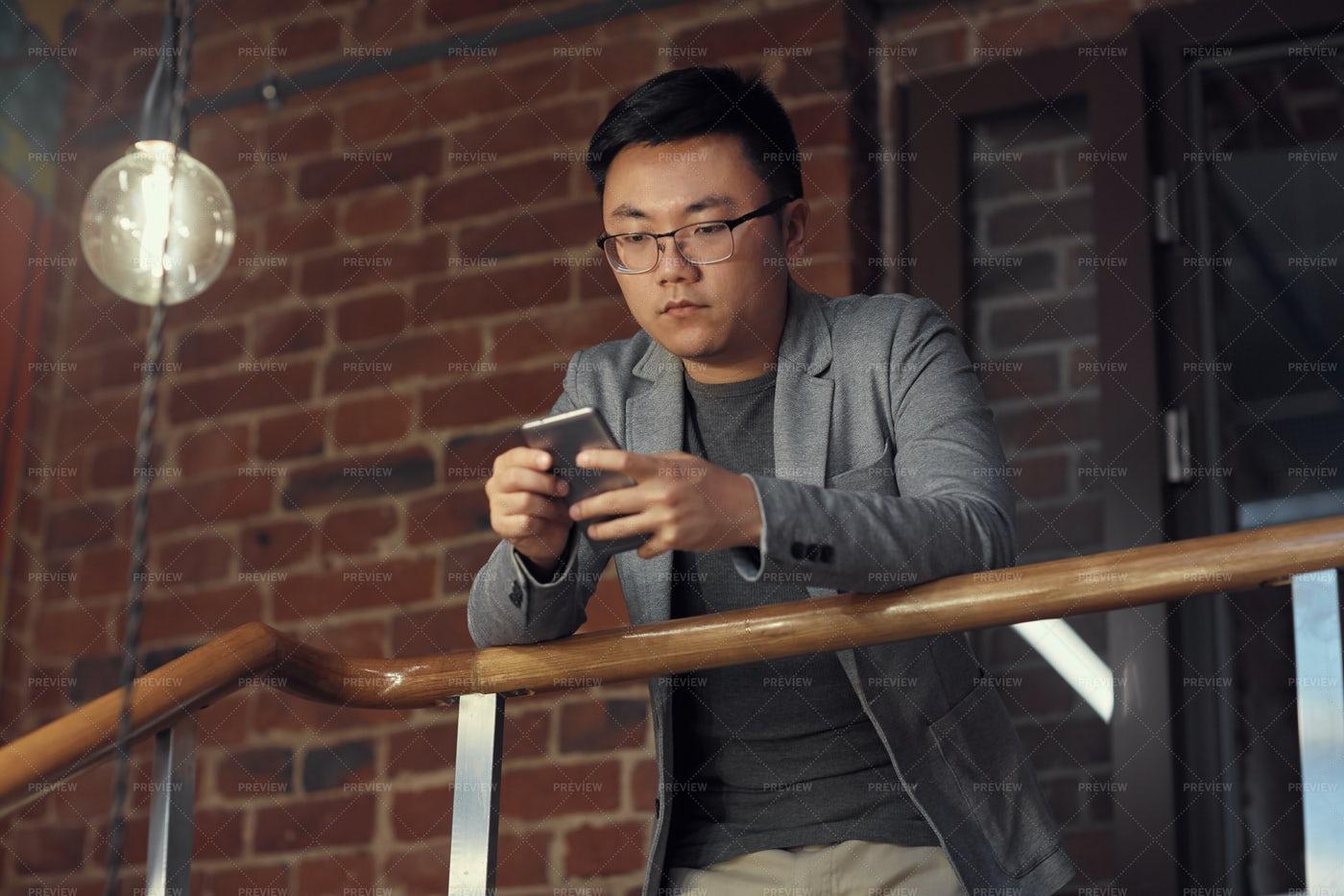 Asian Man Using Smartphone At...: Stock Photos