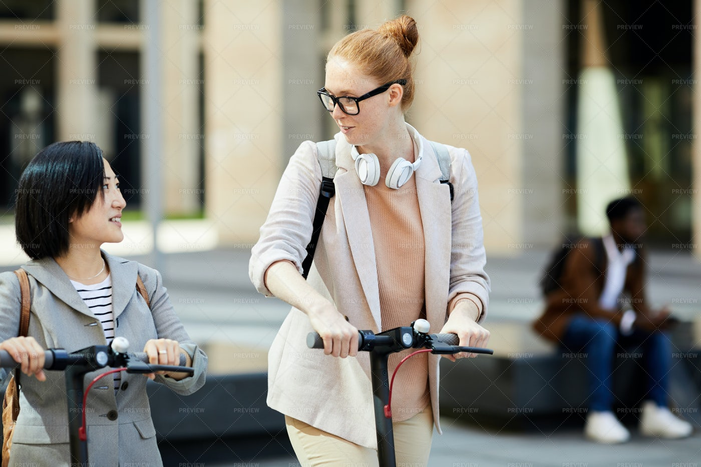Girls Riding Scooters In City: Stock Photos