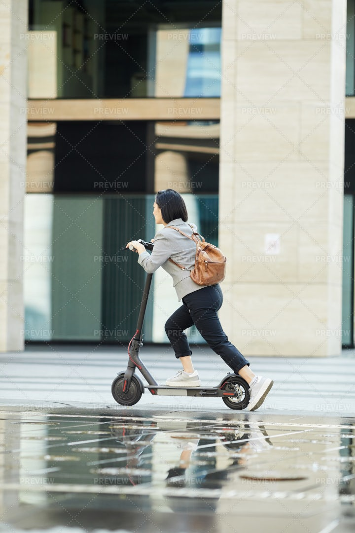 Asian Girl Riding Fast Electric...: Stock Photos