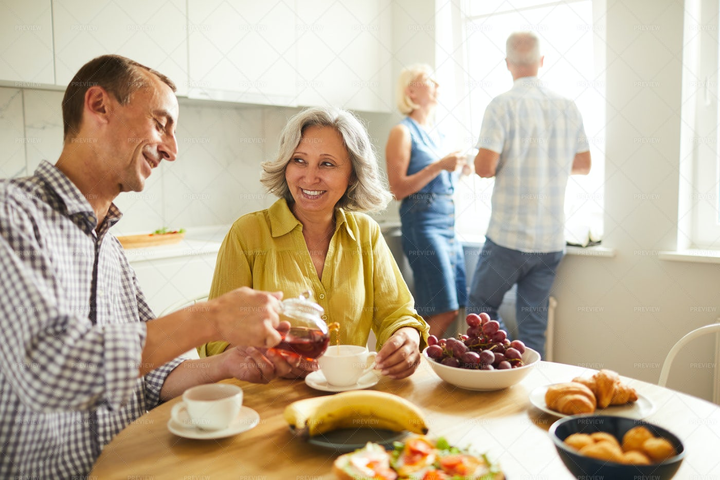 Mixed-Race Senior Couple Drinking...: Stock Photos