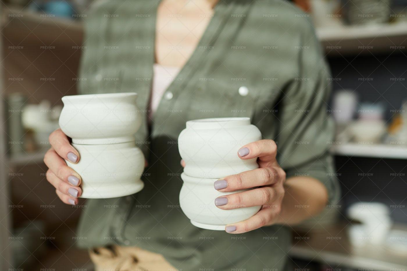 Female Ceramist Holding Pots: Stock Photos