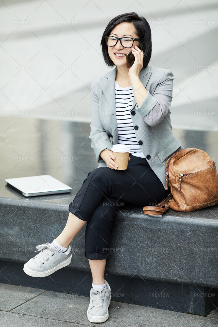 Asian Woman Speaking By Smartphone...: Stock Photos