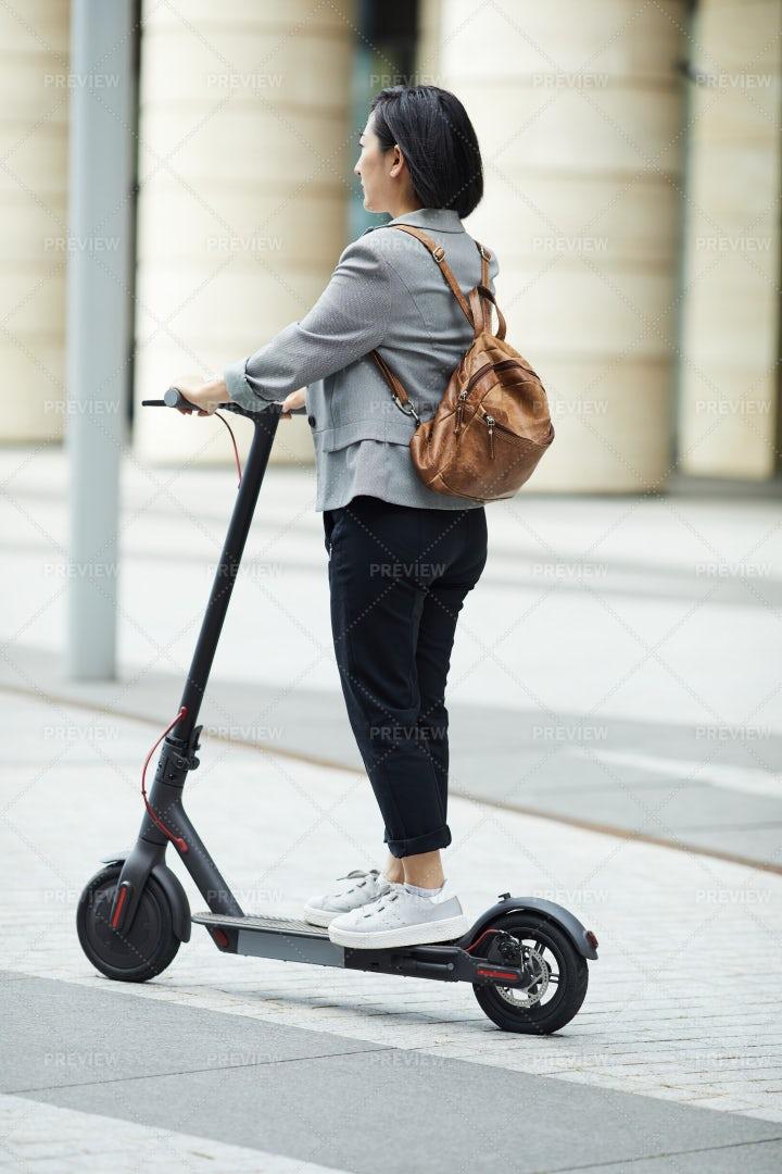 Asian Woman Riding Electric Scooter: Stock Photos