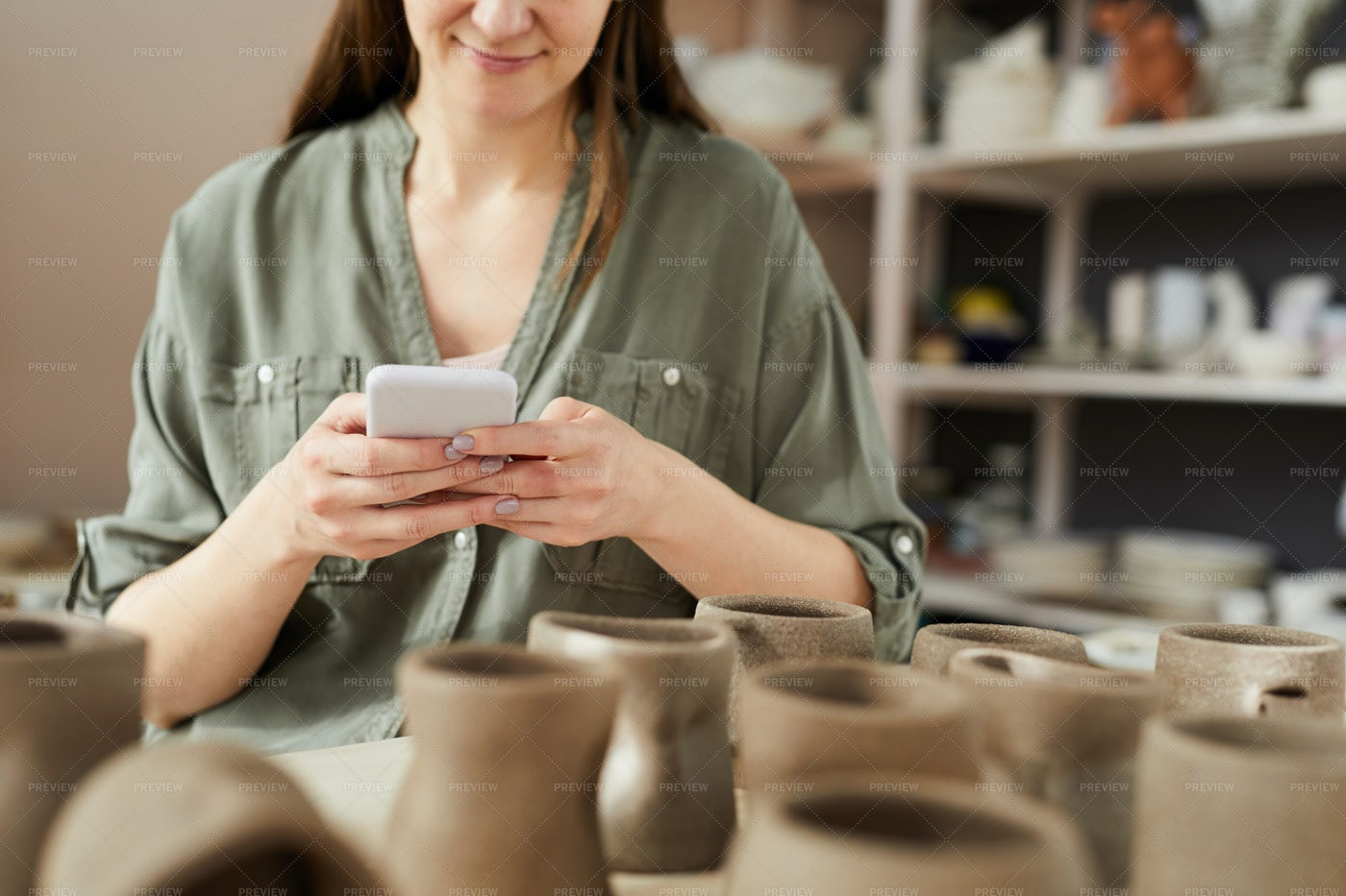 Female Potter Using Smartphone: Stock Photos