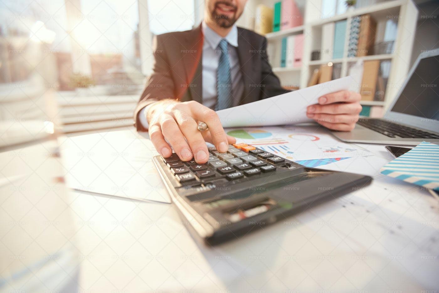 Smiling Businessman Calculating...: Stock Photos