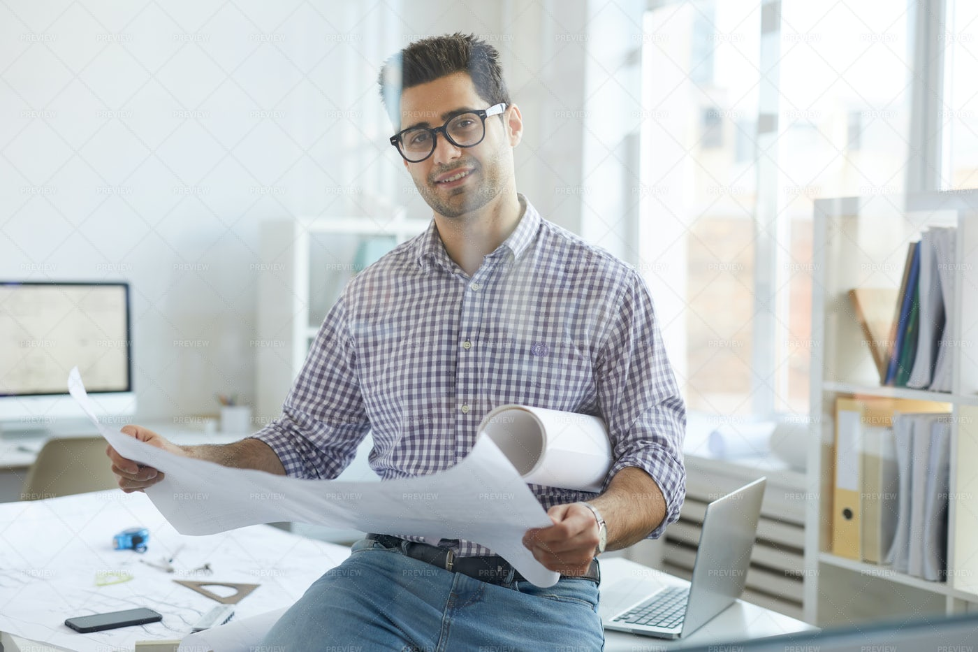 Smiling Engineer Holding Plans  At...: Stock Photos