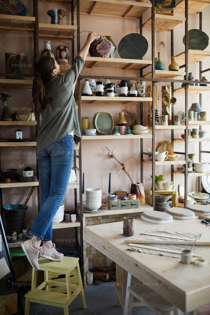 Woman Storing Ceramics On Shelf: Stock Photos