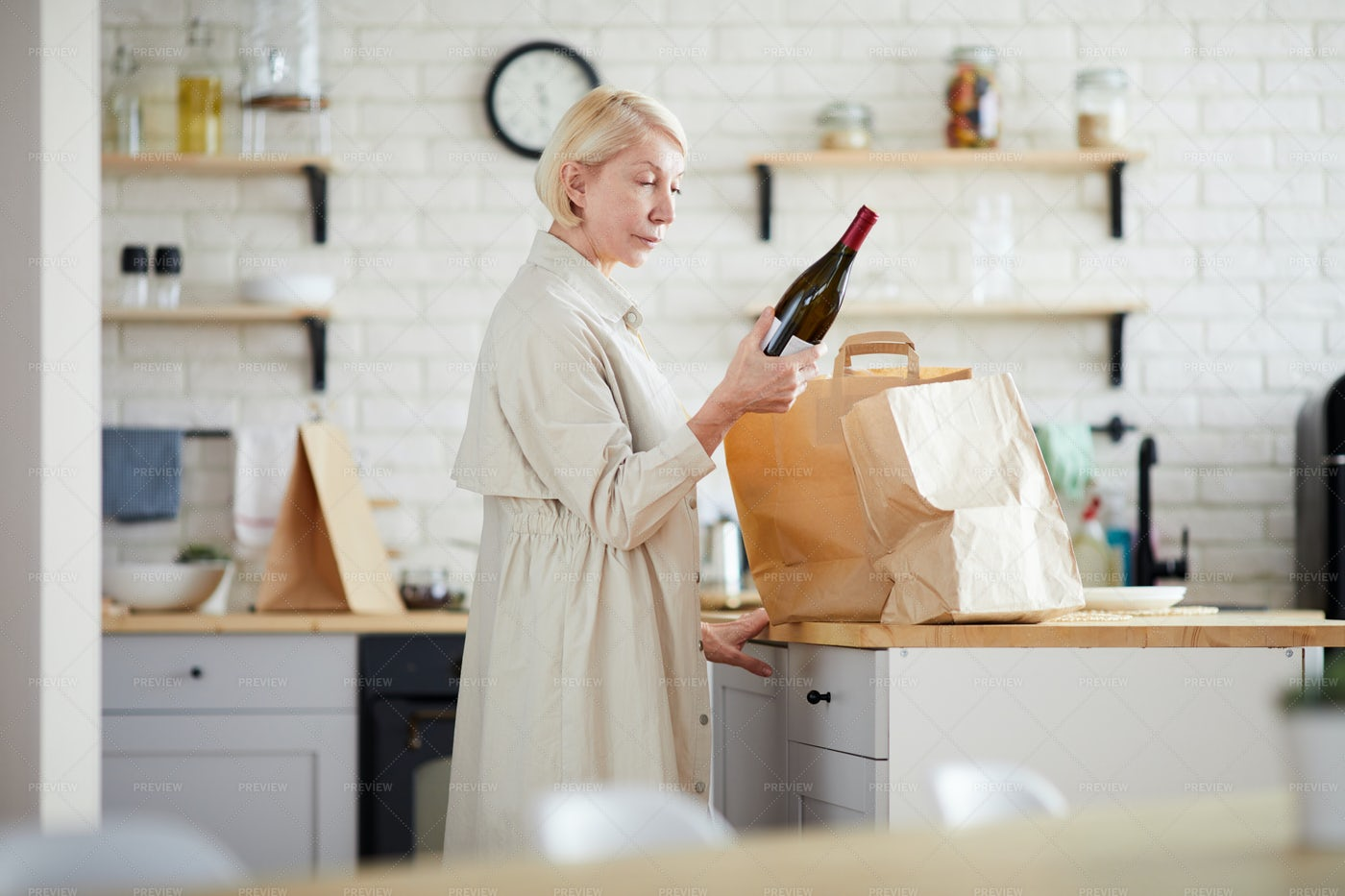 Mature Lady Unpacking Paper Bags In...: Stock Photos