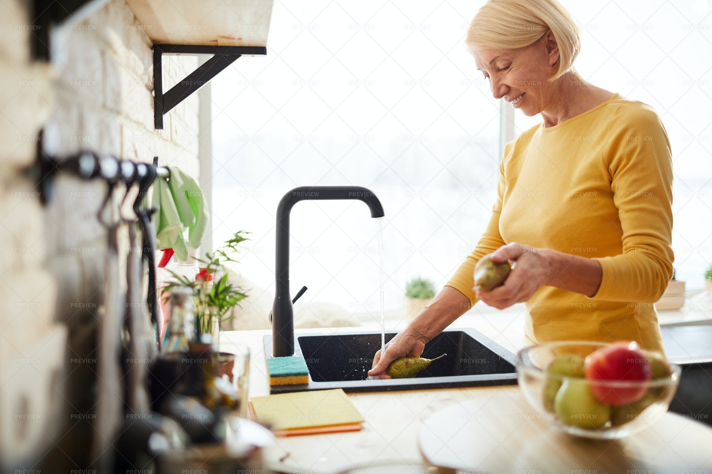 Happy Woman Cleaning Fruits: Stock Photos