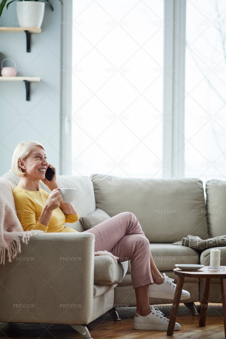 Woman Talking On Phone In Living...: Stock Photos