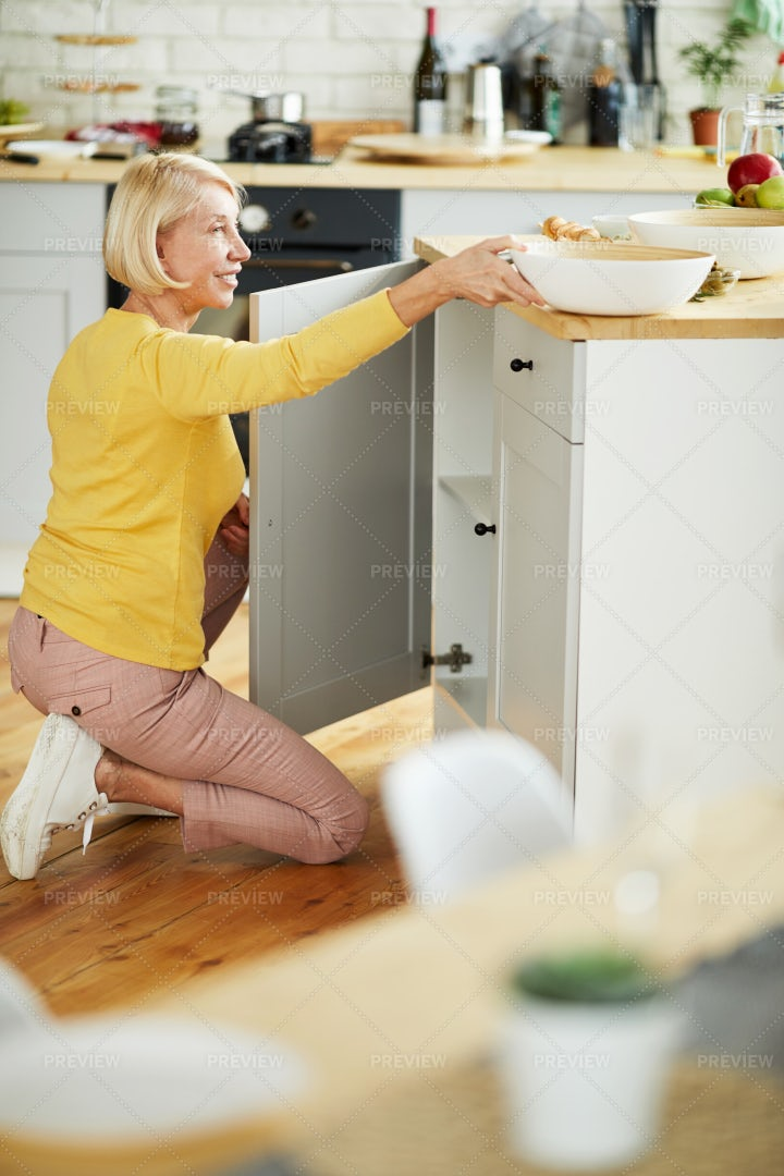 Woman Putting Bowl In Cabinet Box: Stock Photos