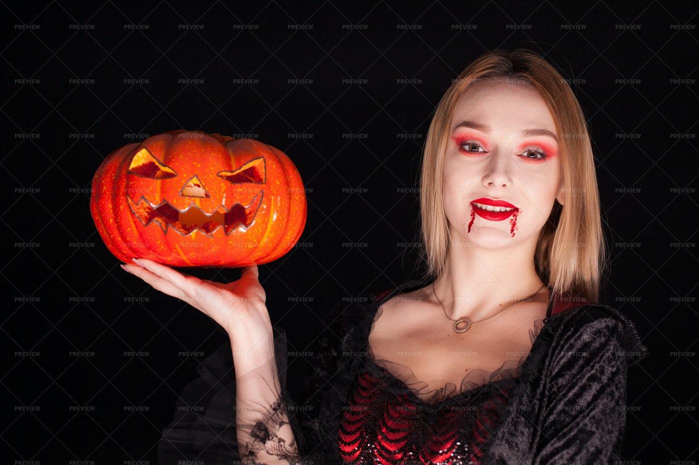 Vampire Woman Holds A Pumpkin: Stock Photos