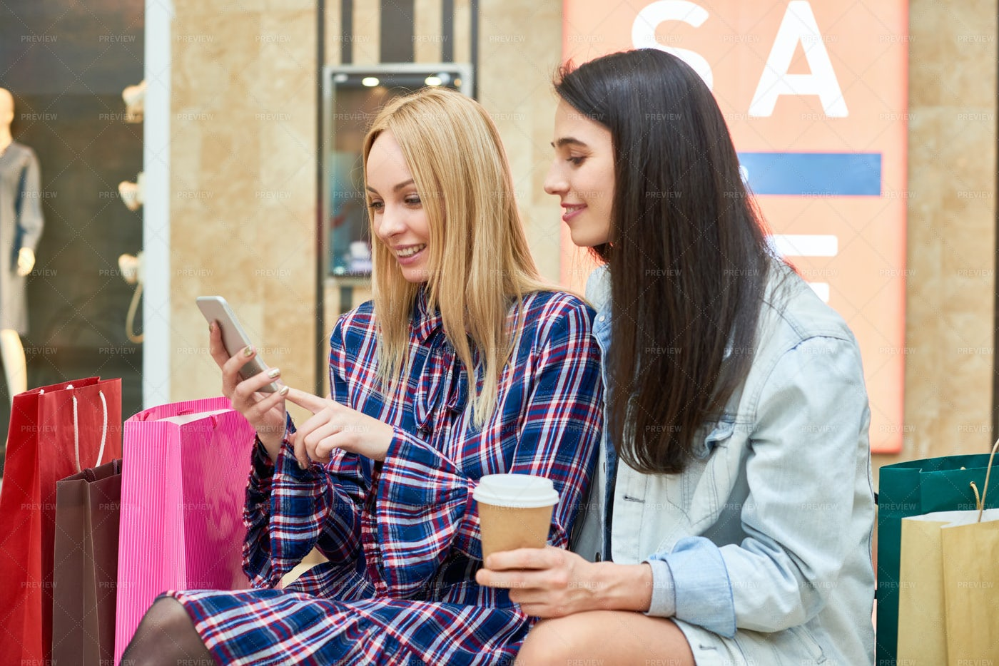 Cheerful Girls Reading About Sales...: Stock Photos