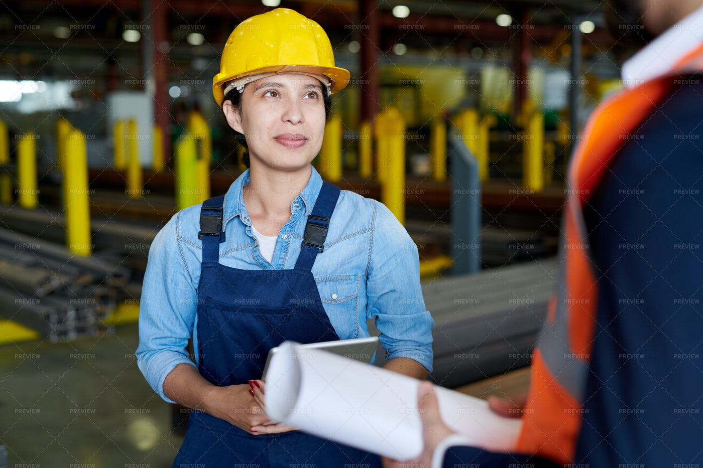Female Factory Worker Listening To...: Stock Photos