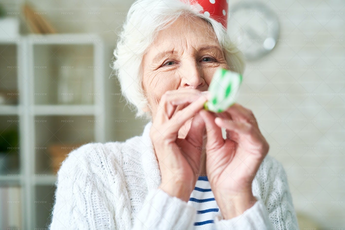 Carefree Granny Blowing Party Horn: Stock Photos