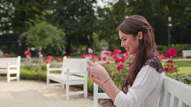 Lady In The Park Gaming On Phone: Stock Video