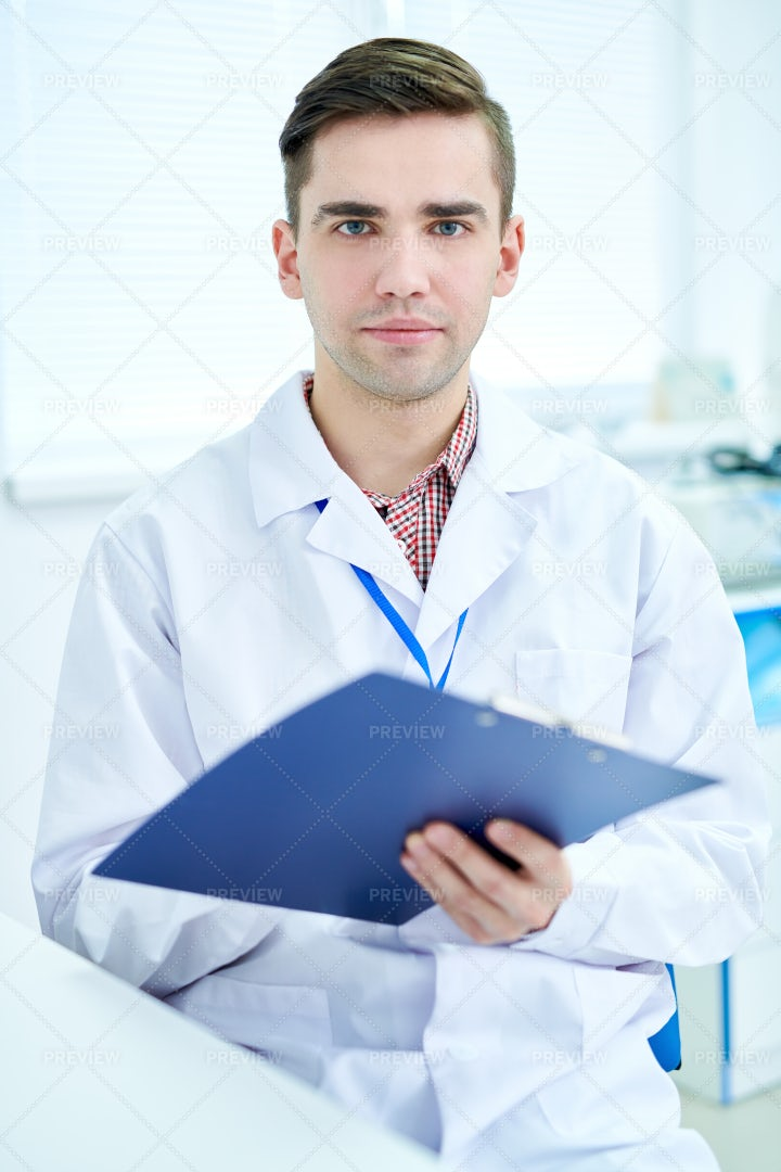 Young Doctor Holding Clipboard: Stock Photos