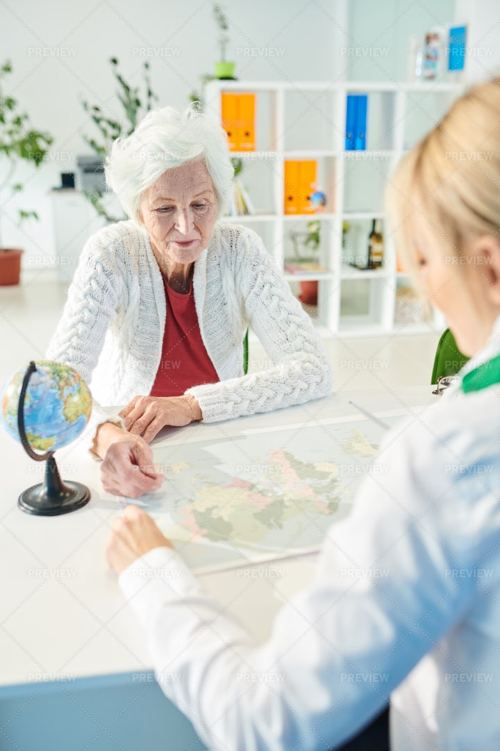 Elderly Lady Asking Travel Agent...: Stock Photos