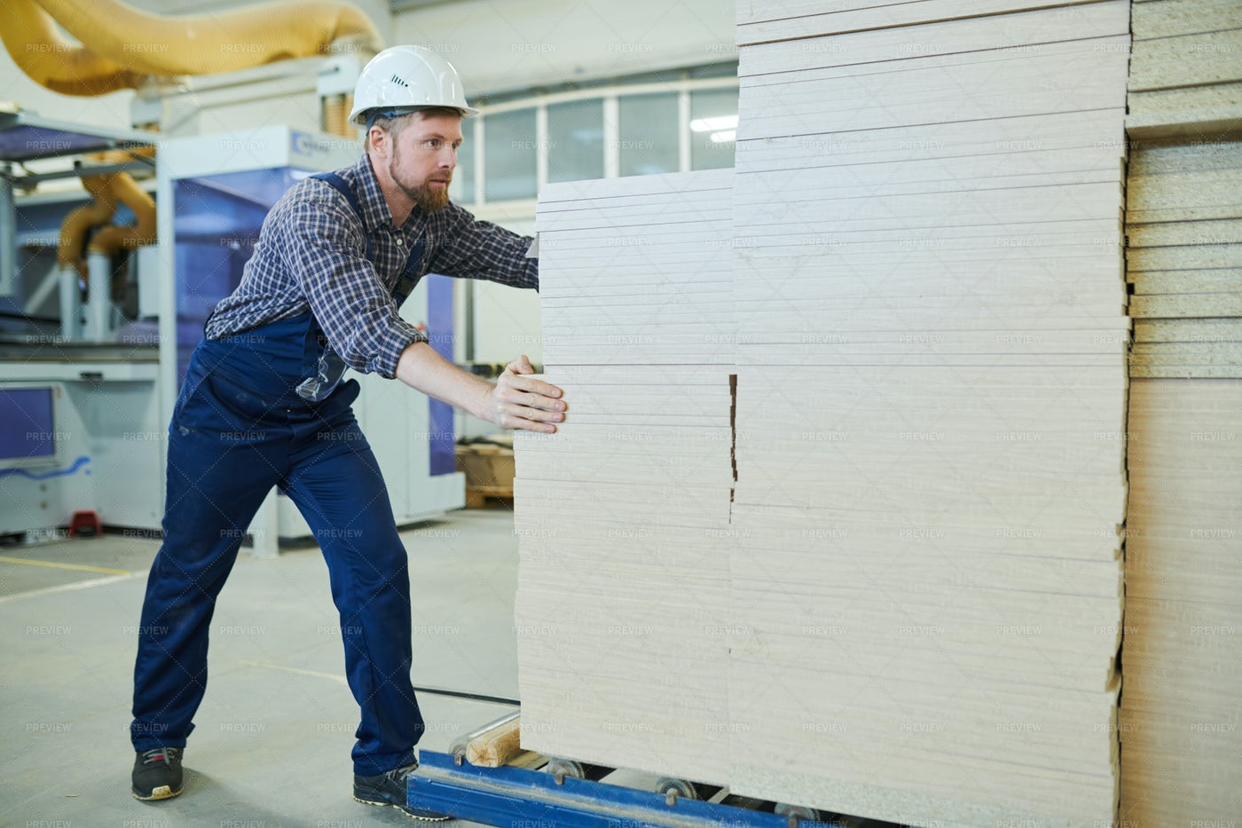 Strong Worker Pushing Stack Of...: Stock Photos