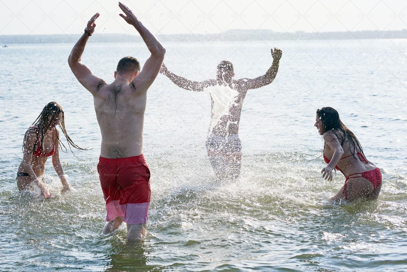 Carefree Friends Having Fun In Sea: Stock Photos
