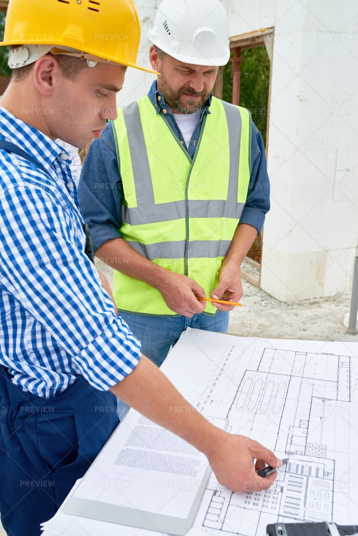 Builders Checking Floor Plans On...: Stock Photos