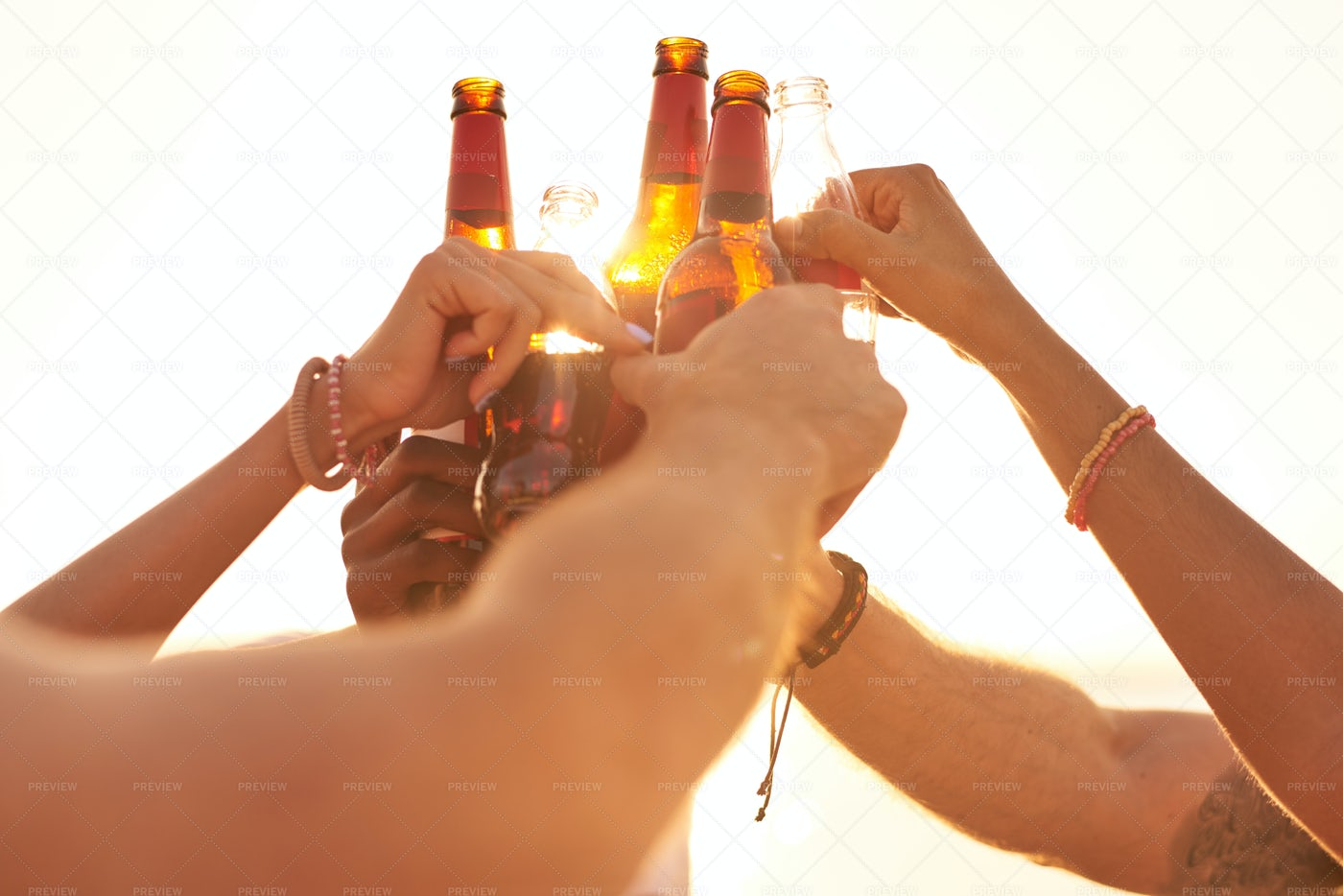 Friends Clinking Beer Bottles In...: Stock Photos