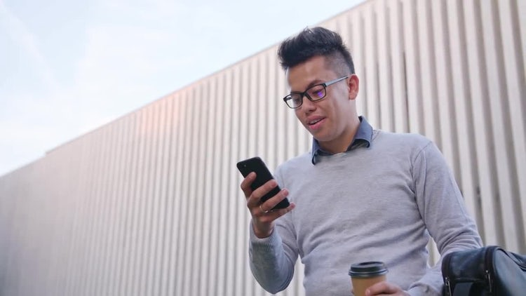 Young Man Using Phone Outside: Stock Video