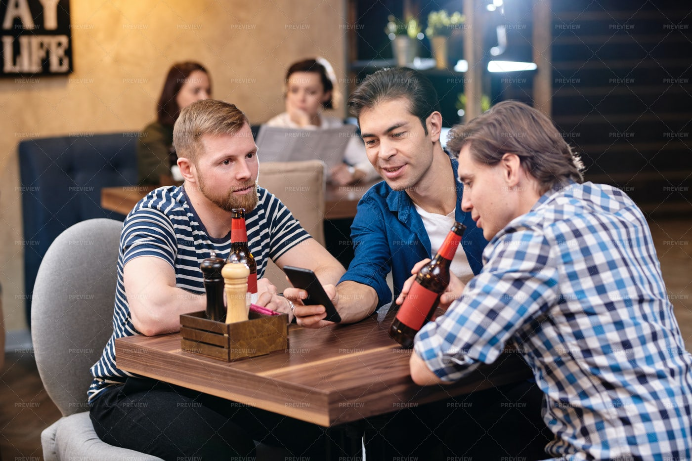 Content Friends Drinking Beer And...: Stock Photos