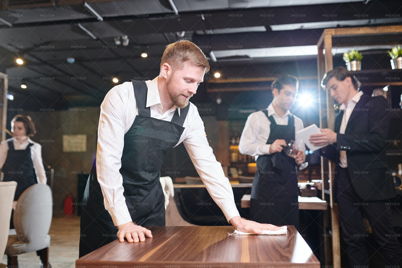 Bearded Waiter Wiping Table In...: Stock Photos