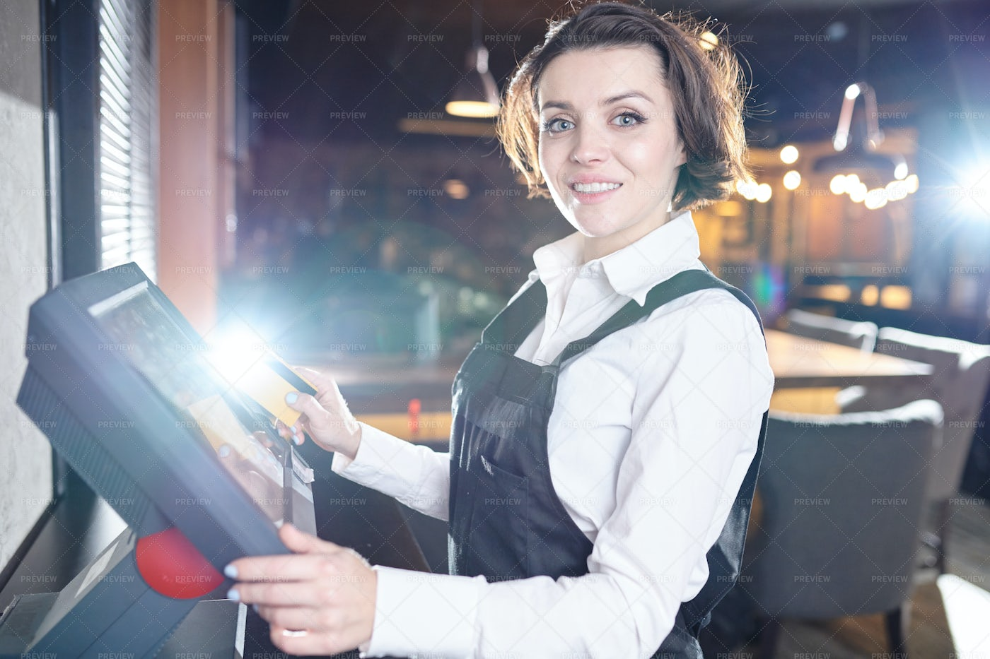 Cheerful Lady Using POS Terminal In...: Stock Photos