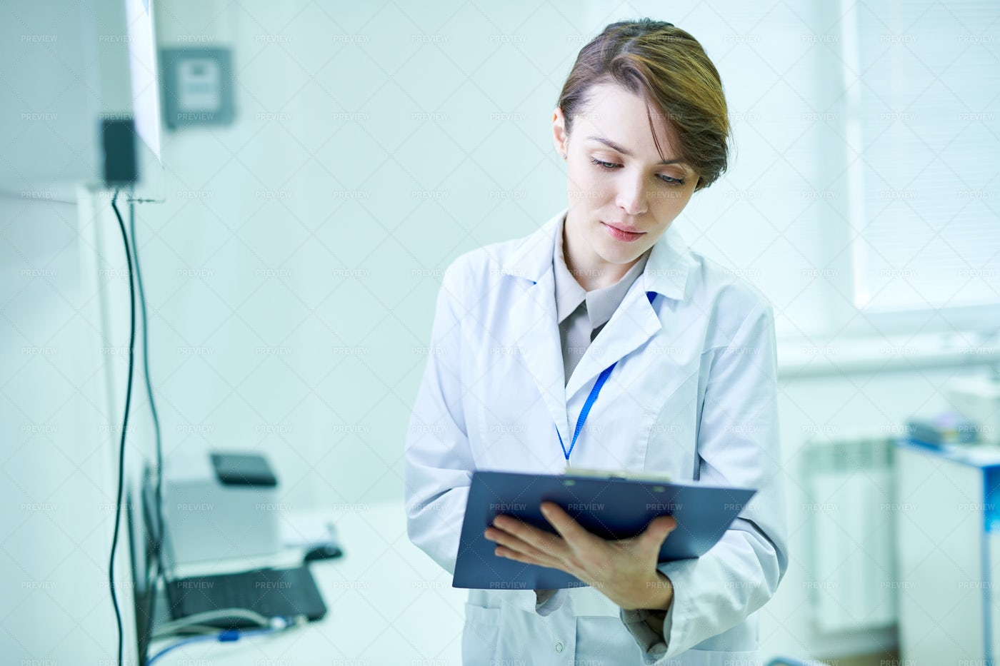 Doctor Standing With Clipboard And...: Stock Photos