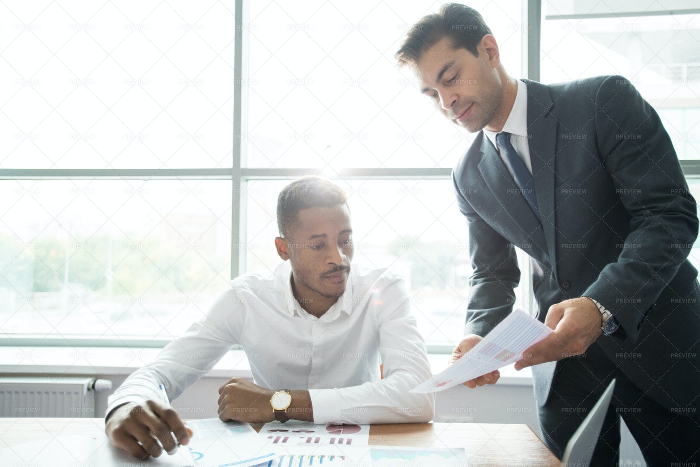 Busy Colleagues Analyzing Charts In...: Stock Photos