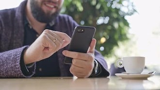 Man Using a Smartphone In Cafe: Stock Video