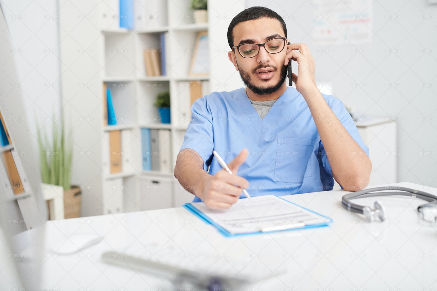 Middle-Eastern Doctor Speaking By...: Stock Photos