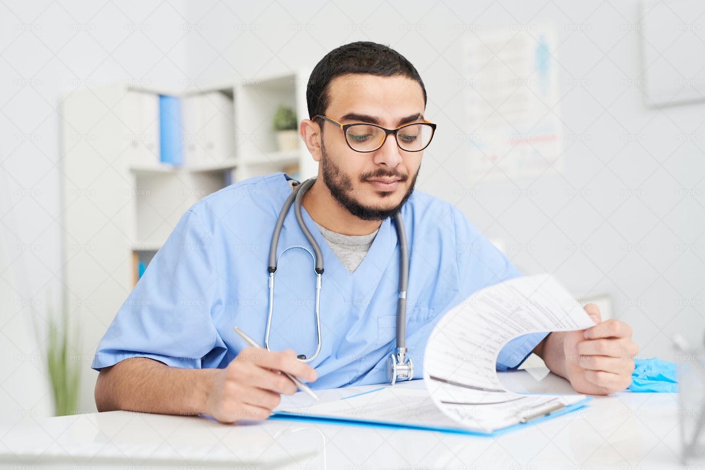 Middle-Eastern Doctor Filling In...: Stock Photos