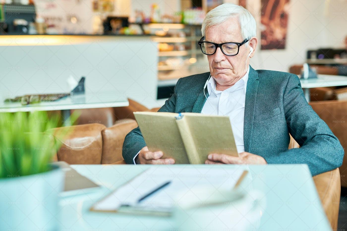 Senior Man Reading Book In Cafe: Stock Photos