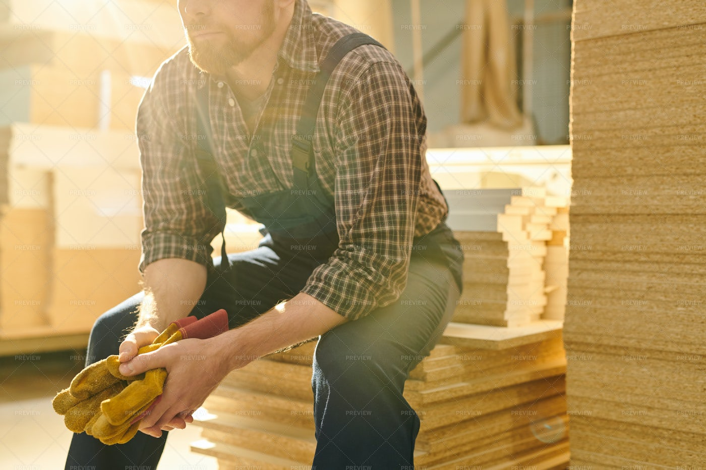 Bearded Worker Sitting On Stack Of...: Stock Photos