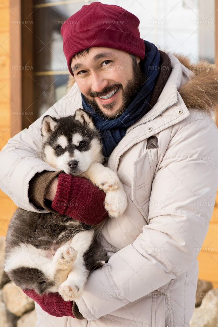 Asian Man Posing With Husky Pup: Stock Photos