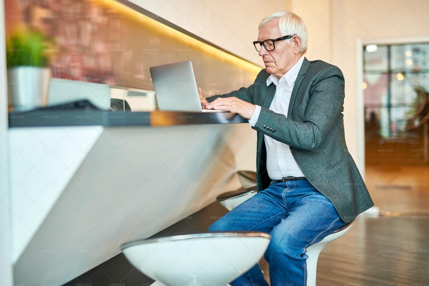 Senior  Businessman Using Laptop In...: Stock Photos